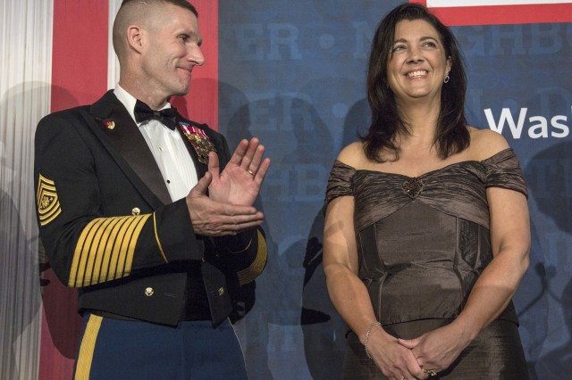 Sgt. Maj. of the Army Daniel Dailey applauds his wife, Holly, as she's honored during a USO awards dinner in Arlington, Va., March 21, 2017. When the Daileys are invited to events, at least a few of them each week are for Holly's projects and the sergeant major of the Army attends them as his wife's spouse, he said.