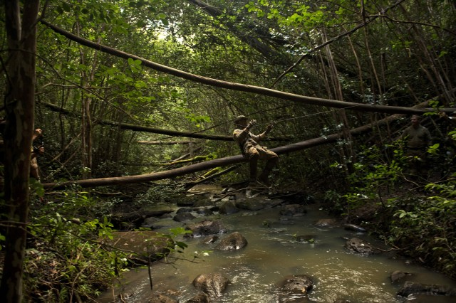 Senior Airman Andrew Schuler uses a rope bridge to cross a creek during a jungle warfare training exercise in Oahu. Airmen learned how to rig and cross the bridge as part of their training with Soldiers.