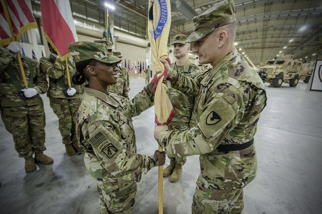 Maj. Gen. Edward Daly (right), commanding general, U.S. Army Sustainment Command, passes the unit colors to Col. Carmelia Scott-Skillern, commander, 401st Army Field Support Brigade during a change of command ceremony for the 401st AFSB at Camp Arifjan, Kuwait, June 30. (U.S. Army Photo by Justin Graff, 401st AFSB Public Affairs)