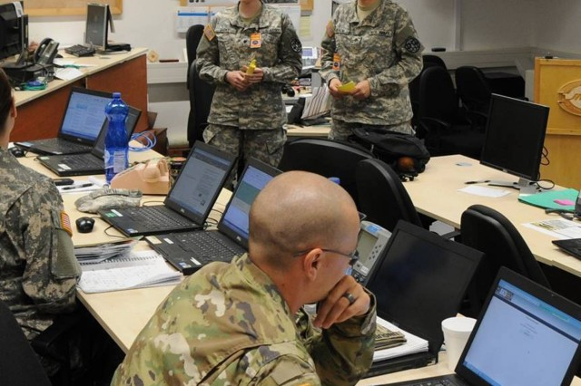 Spc. Sarah Bates, left, and Spc. Selina Copaciu, who are on the HICON J1 staff, brief the Division Tactical Operations Center (DTOC) at Hohefels Training Area, Germany, during a KFOR 23 validation exercise.