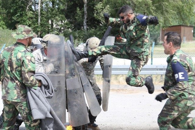 A Portuguese Army Military Police Service Member acting as an aggressive rioter for training purposes jump kicks the riot control shield of a Paratrooper during Fire Phobia training for a Kosovo Force mission rehearsal exercise at the Joint Multinational Readiness Center in Hohenfels, Germany June 23rd, 2017.