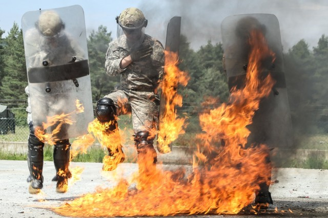 Paratroopers jump and wave their shields to extinguish the fire caught on their equipment during Fire Phobia training for a Kosovo Force mission rehearsal exercise at the Joint Multinational Readiness Center in Hohenfels, Germany June 23rd, 2017.
