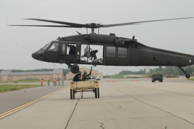 Service members working with U.S Transportation Command and members of the Civil Air Patrol hook a trailer to a UH-60 Black Hawk during a training mission at Scott Air Force Base, Ill. USTRANSCOM conducts training missions to stay proficient at various air operations as well as build a rapport with local emergency services.