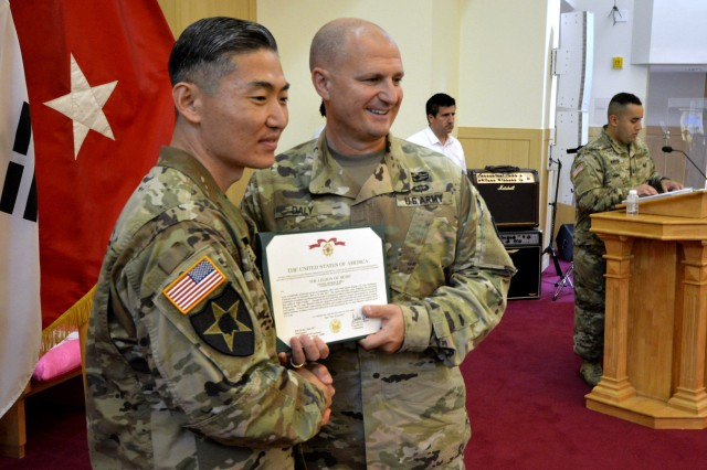 Maj. Gen. Edward M. Daly, Rock Island Arsenal senior commander and commanding general U.S. Army Sustainment Command, presents Col. Mike Siegl, outgoing commander, 403rd Army Field Support Brigade, with the Legion of Merit award during the 403rd's change of command and responsibility ceremony June 28 at Camp Walker in Daegu, Republic of Korea.