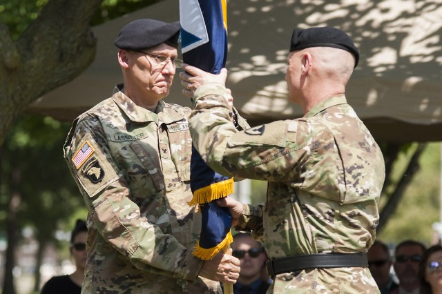 Col. Doyle Lassitter, commander, Distribution Management Center, U.S. Army Sustainment Command, passes the DMC unit colors to Maj. Gen. Edward Daly, senior commander of Rock Island Arsenal and commanding general of ASC, thereby relinquishing his command of the DMC on June 9 in Constitution Square at Rock Island Arsenal, Illinois.