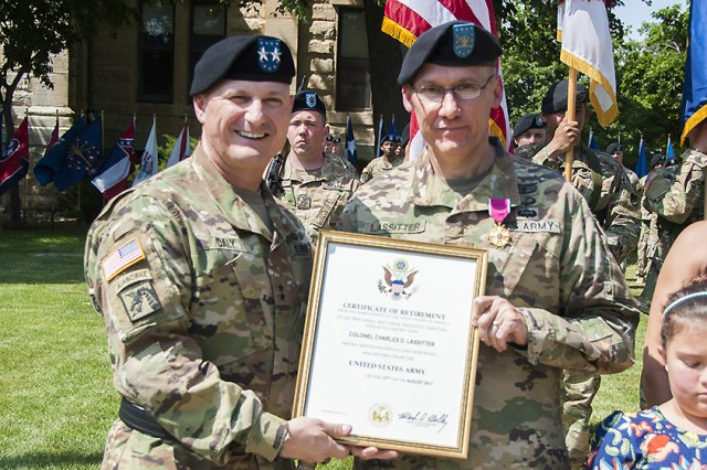 Maj. Gen. Edward Daly, senior commander of Rock Island Arsenal and commanding general of the U.S. Army Sustainment Command, presents Col. Doyle Lassitter, commander, Distribution Management Center, U.S. Army Sustainment Command, with his retirement certificate during the DMC relinquishment of command and retirement ceremony on June 9 in Constitution Square at Rock Island Arsenal, Illinois.