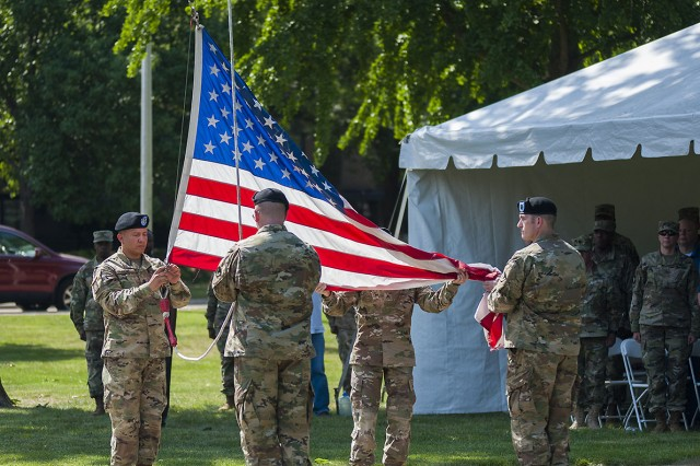 Soldiers retrieve the flag following taps during the Distribution Management Center relinquishment of command ceremony on June 9 in Constitution Square, Rock Island Arsenal, Illinois.