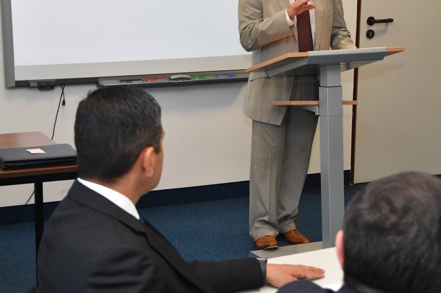 Professor James Howcroft, course director for the Program on Terrorism and Security Studies (PTSS) at the George C. Marshall European Center for Security Studies, tells the seven graduates from six countries that they are now a part of the PTSS family during the graduation ceremony for the English Language Enhancement Course (ELEC) at the Marshall Center July 5. (Marshall Center photo by Karl-Heinz Wedhorn)