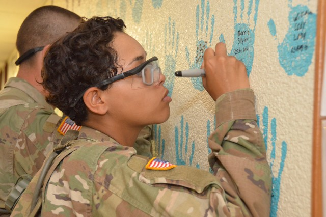 Pvt. Kierra Martin, Company E, 701st Military Police Battalion, signs the SHARP pledge wall located in the company headquarters building.