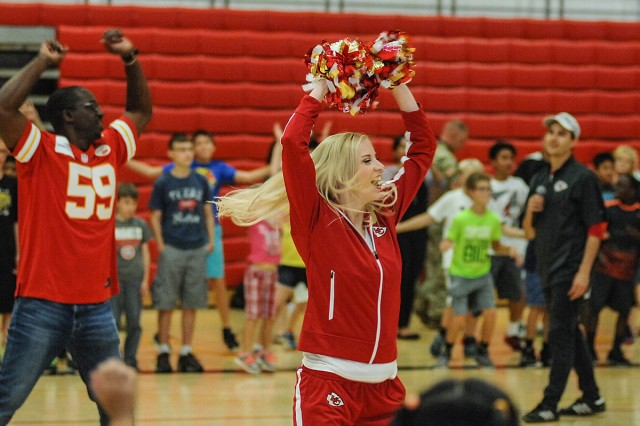 Former Chiefs linebacker Shawn Barber, left, and Chiefs cheerleaders lead participants in jumping jacks. Hundreds of area children turned out for the NFL Play 60 event held Friday at DFC.