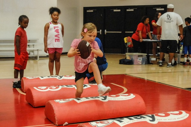 Kaycee Lockard, 4, carries a football over obstacles during the NFL Play 60 with the Kansas City Chiefs event Friday.