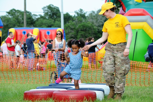 Rania Ortiz, military family member, makes her way through a tire obstacle of the Warrant Officer Career College children's confidence course with the help of Warrant Officer Candidate Ashely Long, WOCC, during Freedom Fest at the festival fields June 30.