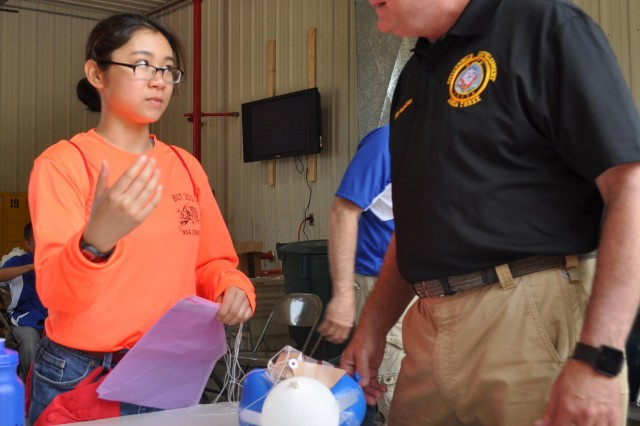 A Navy Junior ROTC student attending the Basic Leadership Training summer camp explains her team's egg drop project. Cadets worked together to create a contraption that would protect the egg during a drop from a three story building without breaking or cracking the egg after learning about the Mars Spirit Rover Landing. The BLT camp was held at Crane Army Ammunition Activity's reserve facility located on Naval Support Activity Crane June 26-30.