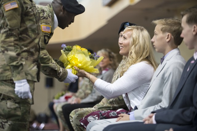 Sgt. Wayne A. Sanders presented a bouquet of yellow roses to Francy Mueller during the June 27 change of command ceremony at U.S. Army Garrison Humphreys. Also shown are Mueller's sons Cooper and Riley.