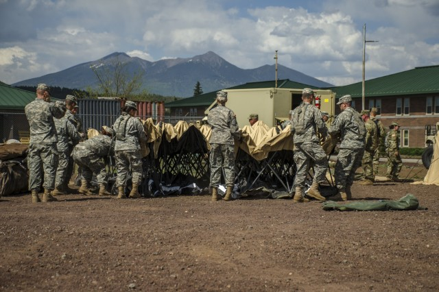 Soldiers from Headquarters and Headquarters Company, 158th Maneuver Enhancement Brigade set up a tent that will become part of the tactical operations center. The unit was conducting annual training at Camp Navajo, Ariz., June 3-17 in preparation of an upcoming Warfighter exercise later this year.