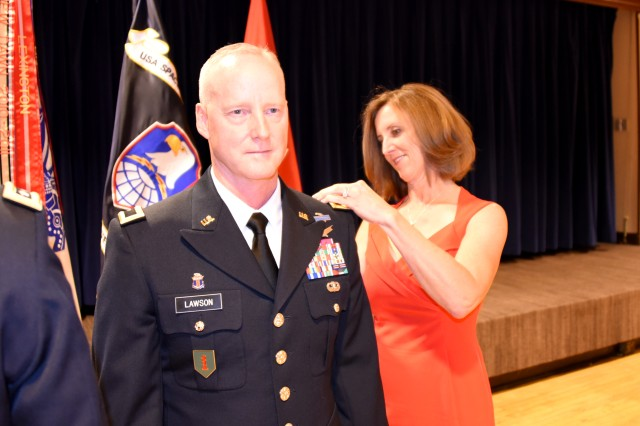 Brig. Gen. Tim C. Lawson, deputy commanding general for operations, U.S. Army Space and Missile Defense Command/Army Forces Strategic Command, receives his one-star rank during a ceremony at the Peterson Air Force Base club July 7 from his wife, Connie.