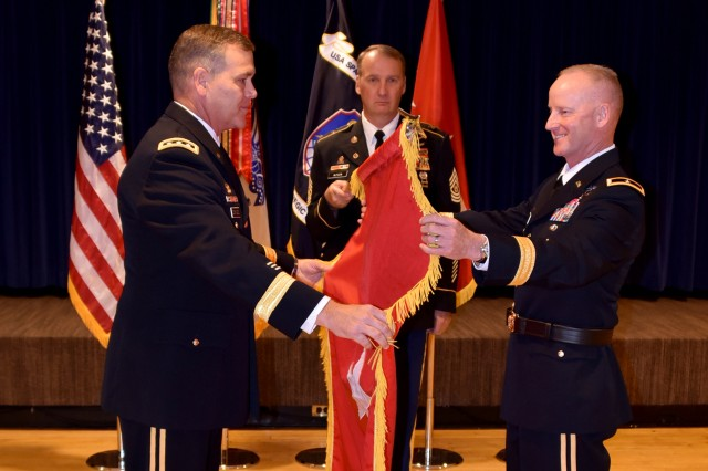 Lt. Gen. James H. Dickinson, right, commanding general, U.S. Army Space and Missile Defense Command/Army Forces Strategic Command, and newly promoted Brig. Gen. Tim C. Lawson,  deputy commanding general for operations, unfurl the one-star flag during a promotion ceremony at the Peterson Air Force Base club July 7.