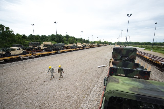 Two Indiana National Guardsman walk down the line to inspect rail cars at Camp Atterbury, In. on July 6, 2017. A group of Guardsmen from Indiana, Illinois and Pennsylvania joined together in support of Task Force Hoosier to assist the 76th Infantry Brigade Combat Team in transporting their equipment to Fort Polk, La. for an upcoming Joint Readiness Training Center Rotation.