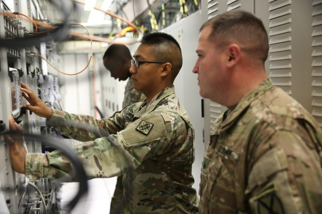 U.S. Army Sgt. Robert Matz, assigned to 10th Combat Aviation Brigade, 10th Mountain Division, observes Spc. Christanjon Burr, assigned to the Enterprise Service Gateway Landstuhl, 102nd Strategic Signal Battalion, 2nd Theater Signal Brigade, while he checks signal connection strengths July 11, 2017 in Landstuhl, Germany. The largest Army-operated SATCOM facility outside the continental U.S., the ESG-L is providing strategic signal support to participants of Saber Guardian 17, a U.S. Army Europe-led, multinational exercise, taking place in Bulgaria, Hungary and Romania July 11-20, 2017.