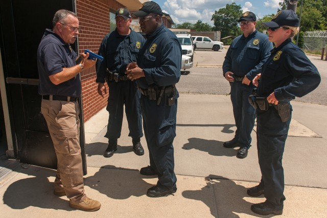 Phil McCombs, instructor, left, provides feedback to students following a building-clearing exercise July 11, 2017 at the U.S. Army Civilian Police Academy at Fort Leonard Wood, Missouri.