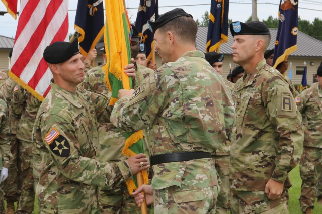 Col. Jack Vantress, left, incoming commander of the 177th Armored Combined Arms Training Brigade, accepts the unit colors from Maj. Gen. Todd McCaffrey, commanding general of First Army Division East, during a change of command ceremony at Camp Shelby, Miss., July 12, 2017. Vantress took over command of the 177th from Col. Brandon Robbins, right, who is headed to a new assignment in Washington, D.C. (U.S. Army photo by Staff Sgt. Rico Frisbie, 177th Armored Combined Arms Training Brigade)
