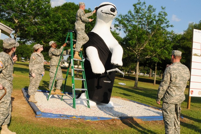 Soldiers from the Fort Rucker Office of the Staff Judge Advocate dress Sgt. Ted E. Bear to represent 'blind justice' in honor of Law Week in 2015.