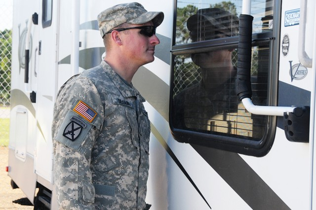 Then-CW2 Justin Seguin, 1-14th Avn. Regt., looks at a recreational vehicle at the Lemon Lot.