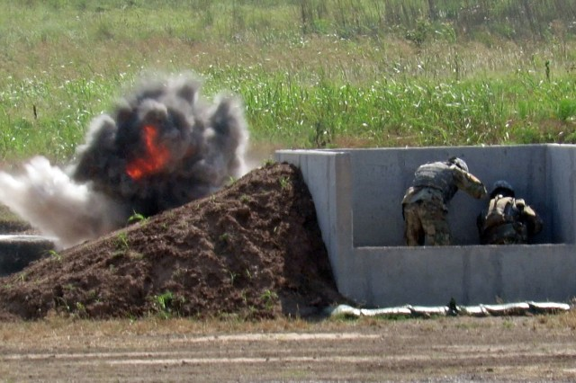 An M67 fragmentation grenade detonates as a basic combat trainee from C/1-79th FA, hunkers down with the instructor June 27,  2017, in pit No. 4 at the Burris Hand Grenade Complex here. Each trainee threw two live grenades following a morning of learning to arm and throw practice grenades during their fifth week of basic combat training.