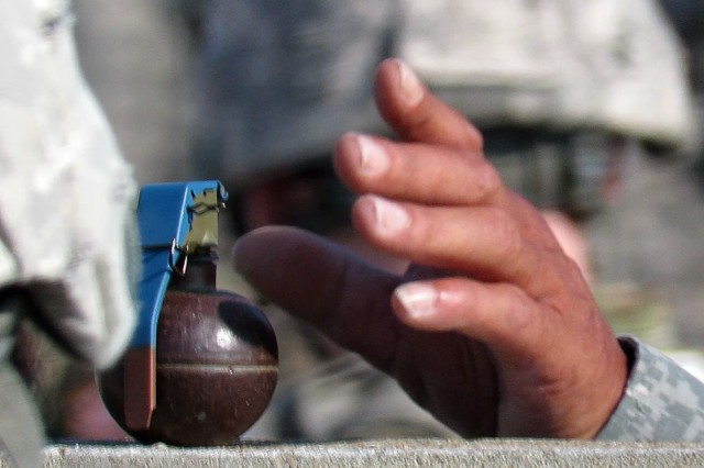 A 434th Field Artillery Detachment instructor prepares to give an M69 practice hand grenade to a trainee.