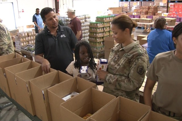 Fort Knox Soldiers fill cardboard boxes with nonperishable food items at Feeding America in Elizabethtown. The volunteers were able to help 366 families with the food that was packed.
