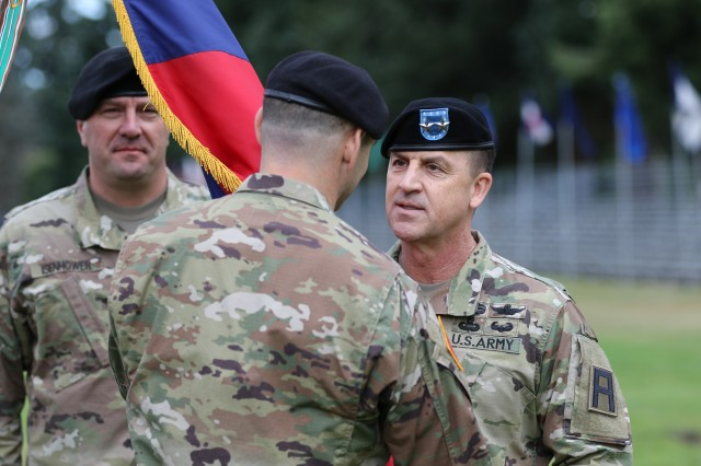 Maj Gen. Erik C. Peterson (right), commanding general, Division West, passes the brigade colors to Col. Roland H Dicks, incoming commander for the 189th Combined Arms Training Brigade, during a change of command ceremony on Watkins Field, Joint base Lewis-McChord, Wash., July 13. (U.S. Army photo by Sgt. 1st Class Reshema G. Sherlock)