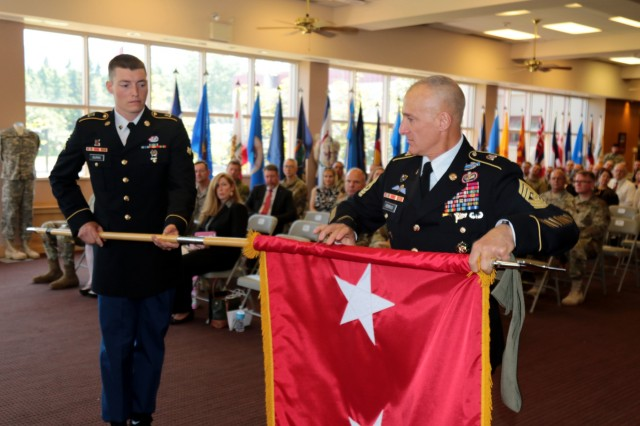 Command Sgt. Maj. Michael A. Ferrusi, senior enlisted advisor for U.S. Army Alaska, furls the general officer flag of Maj. Gen. Bryan R. Owens, the former commander of USARAK during the latter's retirement ceremony at Joint Base Elmendorf-Richardson's Fireside Room July 12. Owens retired after a 34-year career later that day.