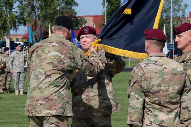 Gen. Robert Brown, the commander of United States Army Pacific, passes the U.S. Army Alaska unit colors to Maj. Gen. Mark O'Neil, the new commander of USARAK, during a change of command ceremony at Joint Base Elmendorf-Richardson's Pershing Field July 12. O'Neil took command of USARAK after serving as the Chief of Staff for USARPAC.