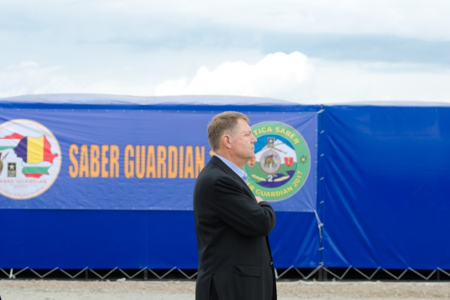 Romanian President Klaus Iohannis renders respect for the playing of the Romanian National Anthem during Distinguished Visitors Day for Getica Saber, July 15, 2017 in Cincu, Romania. Getica Saber 17 is a U.S.-led fire support coordination exercise and combined arms live fire exercise that incorporates six Allied and partner nations with more than 4,000 Soldiers. Getica Saber 17 runs concurrent with Saber Guardian 17, a U.S. European Command, U.S. Army Europe-led multinational exercise that spans across Bulgaria, Hungary and Romania with more than 25,000 service members from 22 Allied and partner nations
