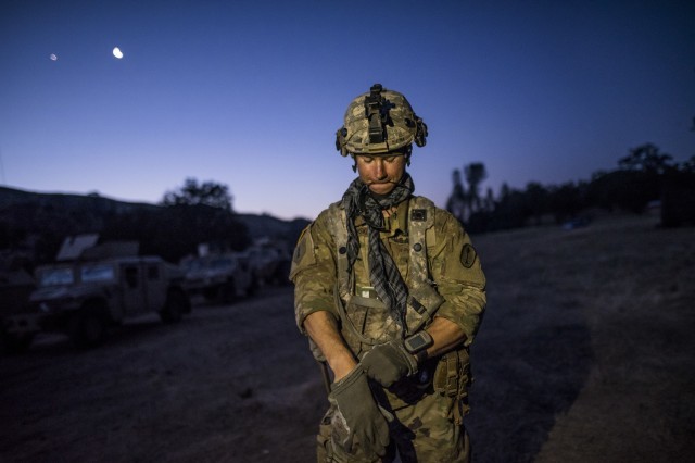 Spc. Drake Klarkowski, of Moline, Illinois, a U.S. Army Reserve Soldier with the 339th Military Police Company (Combat Support), headquartered in Davenport, Iowa, puts on his gloves to prepare for a route reconnaissance during a Warrior Exercise (WAREX) held at Fort Hunter Liggett, California, June 20. The MP company's Soldiers had to relocate their tactical assembly areas in the field multiple times as they reconnoitered different areas of their operational environment, while fighting against temperatures reaching 100-plus degrees daily. (U.S. Army Reserve photo by Master Sgt. Michel Sauret)