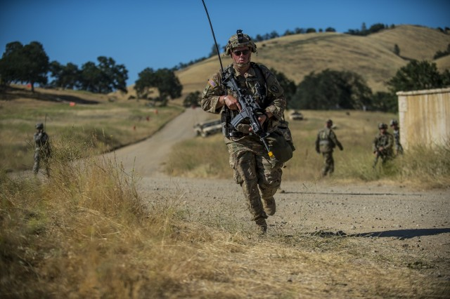"""Staff Sgt. Nick Simonson, a U.S. Army Reserve platoon sergeant for the 339th Military Police Company (Combat Support), headquartered in Davenport, Iowa, runs to an """"injured"""" Soldier during a route reconnaissance training event as part of their Warrior Exercise (WAREX) held at Fort Hunter Liggett, California, June 19. The MP company's Soldiers had to relocate their tactical assembly areas in the field multiple times as they reconnoitered different areas of their operational environment, while fighting against temperatures reaching 100-plus degrees daily. (U.S. Army Reserve photo by Master Sgt. Michel Sauret)"""