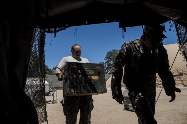 """U.S. Army Reserve Soldiers from the 384th Military Police Battalion, headquartered in Fort Wayne, Indiana, break down and load up their operational tents in response to an """"inject"""" in the middle of their Warrior Exercise (WAREX) held at Fort Hunter Liggett, California, June 19. The MP battalion's Soldiers and leadership originally arrived thinking they would train on detainee and enemy prisoner of war operations, but instead they were tasked to train on housing displaced civilians during a two-week WAREX, with temperatures reaching 100-plus degrees daily. (U.S. Army Reserve photo by Master Sgt. Michel Sauret)"""