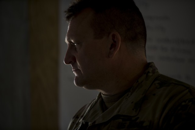 Maj. Travis Gilbert, U.S. Army Reserve operations officer in charge for the 384th Military Police Battalion, headquartered in Fort Wayne, Indiana, listens to a Soldier briefing information during a Warrior Exercise (WAREX) held at Fort Hunter Liggett, California, June 19. The MP battalion's Soldiers and leadership originally arrived thinking they would train on detainee and enemy prisoner of war operations, but instead they were tasked to train on housing displaced civilians during a two-week WAREX, with temperatures reaching 100-plus degrees daily. (U.S. Army Reserve photo by Master Sgt. Michel Sauret)