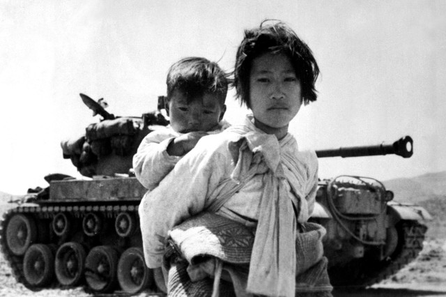 With her brother on her back a war weary Korean girl tiredly trudges by a stalled tank, in Haengju, Korea, June 9, 1951.