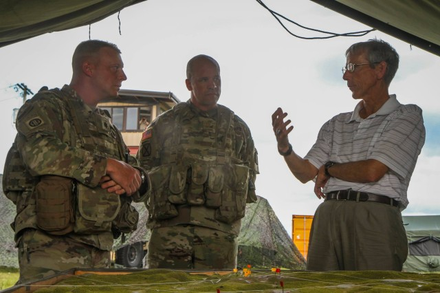 Leaders from 4th Battalion, 31st Infantry Regiment, 1st Brigade Combat Team, 10th Mountain Division (left) brief Acting Secretary of the Army Robert Speer (right) on the unit's training operations at Fort Drum's Range 48 on Wednesday, July 12 at Fort Drum, N.Y.