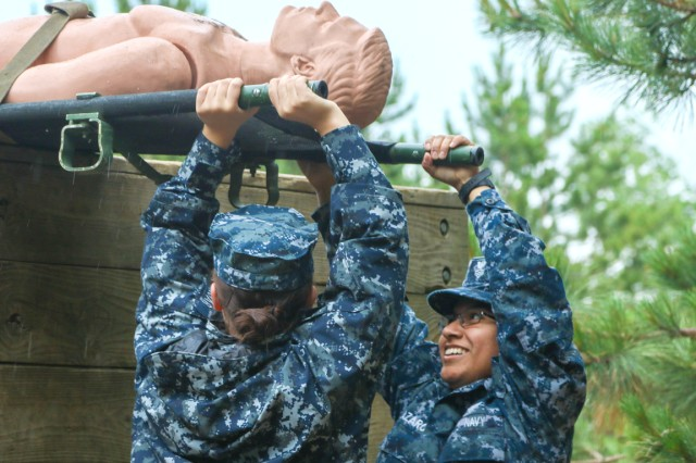 A team of Naval Reservists learn Tactical Combat Casualty Care and how to properly move a loaded stretcher over a wall obstacle during the fourth annual Operation Commanding Force, a joint-service training event between the Portsmouth Naval Reserves and Active Army medical personnel at the Medical Simulation Training Center at Fort Drum.