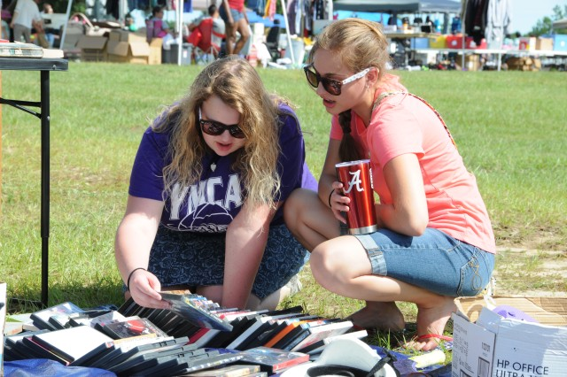 Hannah Davidson and Sierra John, military family members, rummage through old DVDs during the Fort Rucker Outdoor Yard Sale at the festival fields July 15.