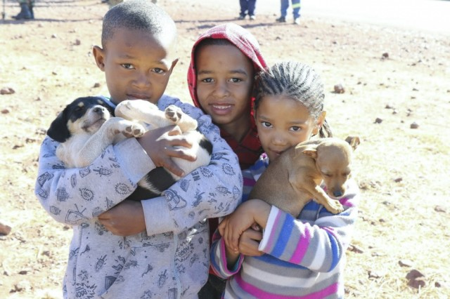 Resident children from the shanty town of Postmasburg, South Africa bring their pets to a free dog clinic July 18 in celebration of Nelson Mandela International Day 2017. U.S. Army Africa Command (USARAF) Soldiers, troops from the 101st Airborne Division (Air Assault), and service members from the South African National Defense Force, who are taking part in Exercise Shared Accord 2017, partnered with the Diere Forum Postmasburg animal shelter to volunteer 67 minutes of their time in service to the community to commemorate Mandela Day.