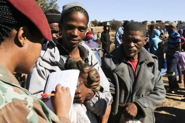 A South African National Defense Force soldier takes down the information of a Postmasburg, South Africa resident during a free dog clinic July 18 in celebration of Nelson Mandela International Day 2017. U.S. Army Africa Command (USARAF) Soldiers, troops from the 101st Airborne Division (Air Assault), and servicemembers from the South African National Defense Force, who are taking part in Exercise Shared Accord 2017, partnered with the Diere Forum Postmasburg animal shelter to volunteer 67 minutes of their time in service to the community.