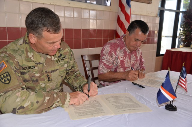 Lt. Gen. James H. Dickinson, commanding general, U.S. Army Space and Missile Defense Command/Army Forces Strategic Command, signs an implementing arrangement with John Silk, Republic of the Marshall Islands foreign minister July 12 on Kwajalein Atoll. The agreement will give the Marshallese burial and gardening rights on islands in the mid-atoll corridor.