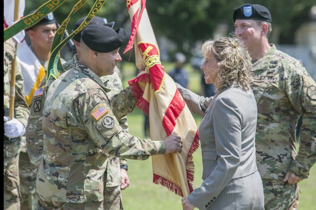 Dr. Christine T. Altendorf, regional director of IMCOM-Pacific, passes the USAG Japan guidon to Col. Phillip K. Gage, incoming USAG Japan commander, during a change of command ceremony held July 21 at  Camp Zama's Yano Field. (U.S. Army photo by Honey Nixon)