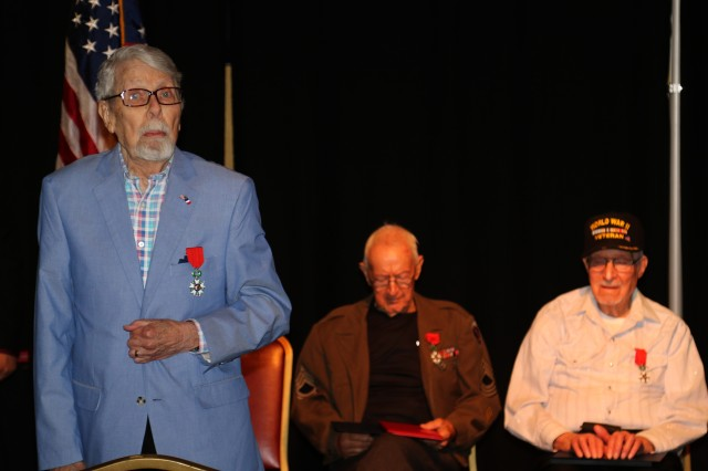 Rober Stava, wearing the French Legion of Honor Medal, leads in the singing of God Bless America at a ceremony presenting the Legion of Honor Medal to Master Sgt. Kyle Wells and Pfc. Vernon Fulcher