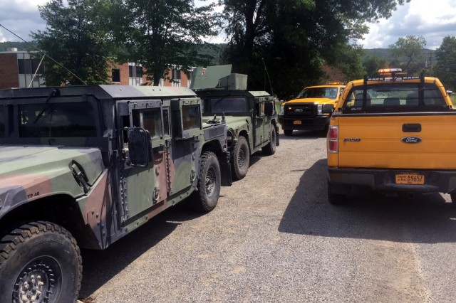 New York Army National Guard Humvees assemble alongside the Erie County Highway Department vehicles near Holland, New York following tornado storm damage on July 20, 2017. New York Army National Guard Engineers from Company A, 27th Brigade Special Troops Battalion deployed from their home station in Lockport, New York as part of a 100-member joint National Guard response element to assist local emergency responders with recovery efforts. A tornado touched down in Erie County in Western New York State, leaving an initial 20,000 residents without power and downing powerlines and trees, blocking local roads with debris.