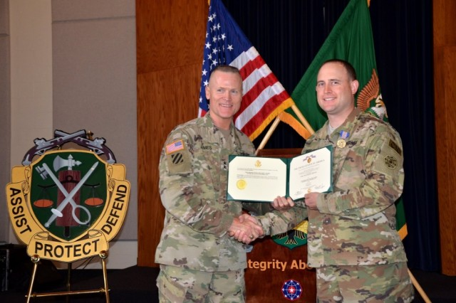 Maj. Gen. Thomas James Jr., 7th Infantry Division commander, left, awards CW3 Jesse Rhymes the Soldier's Medal on July 13 for saving the life of a man who was trapped inside a burning vehicle.