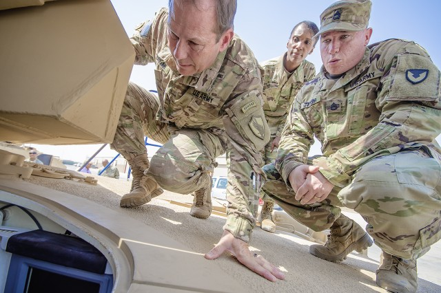 Maj. Gen. Edward Dorman (left), J-4 (logistics), U.S. Central Command, looks at a combat configured tank with Sgt. 1st Class Frank Taylor, contract officer representative, Army Field Support Battalion-Kuwait and Col. Carmelia Scott-Skillern, commander, 401st Army Field Support Brigade during a tour of an Army Prepositioned Stocks-5 warehouse at Camp Arifjan, Kuwait, July 20. (U.S. Army Photo by Justin Graff, 401st AFSB Public Affairs)